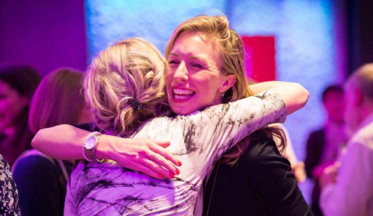 women hugging at Impact Awards