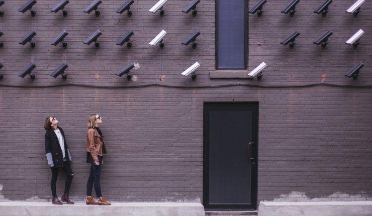 women standing under video surveillance