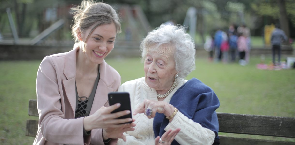 young lady and elderly using a mobile phone
